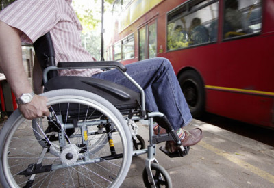 Disabled man in wheelchair at London bus stop